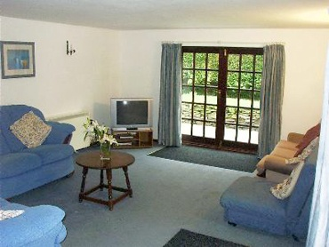 Large lounge with french windows leading to a slate terrace and cottage garden