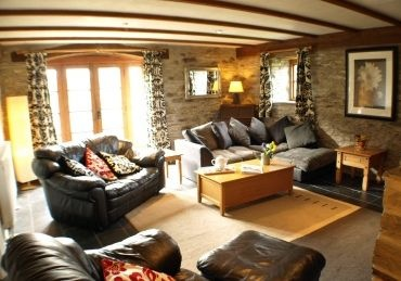 Sitting room is cosy with rugs on a slate floor and wood burning stove