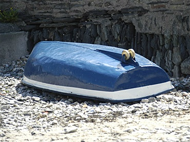 Blue dinghy stored above the tide line on the beach