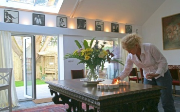 Lighting candles to welcome guests to breakfast in the dining room at Dormy House