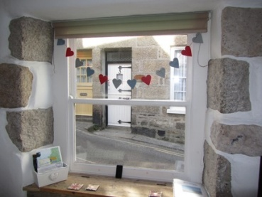 Sash window in the sitting room with view to an old cottage opposite